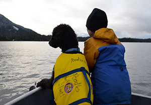 Dog and boy on boat in Southeast Alaska